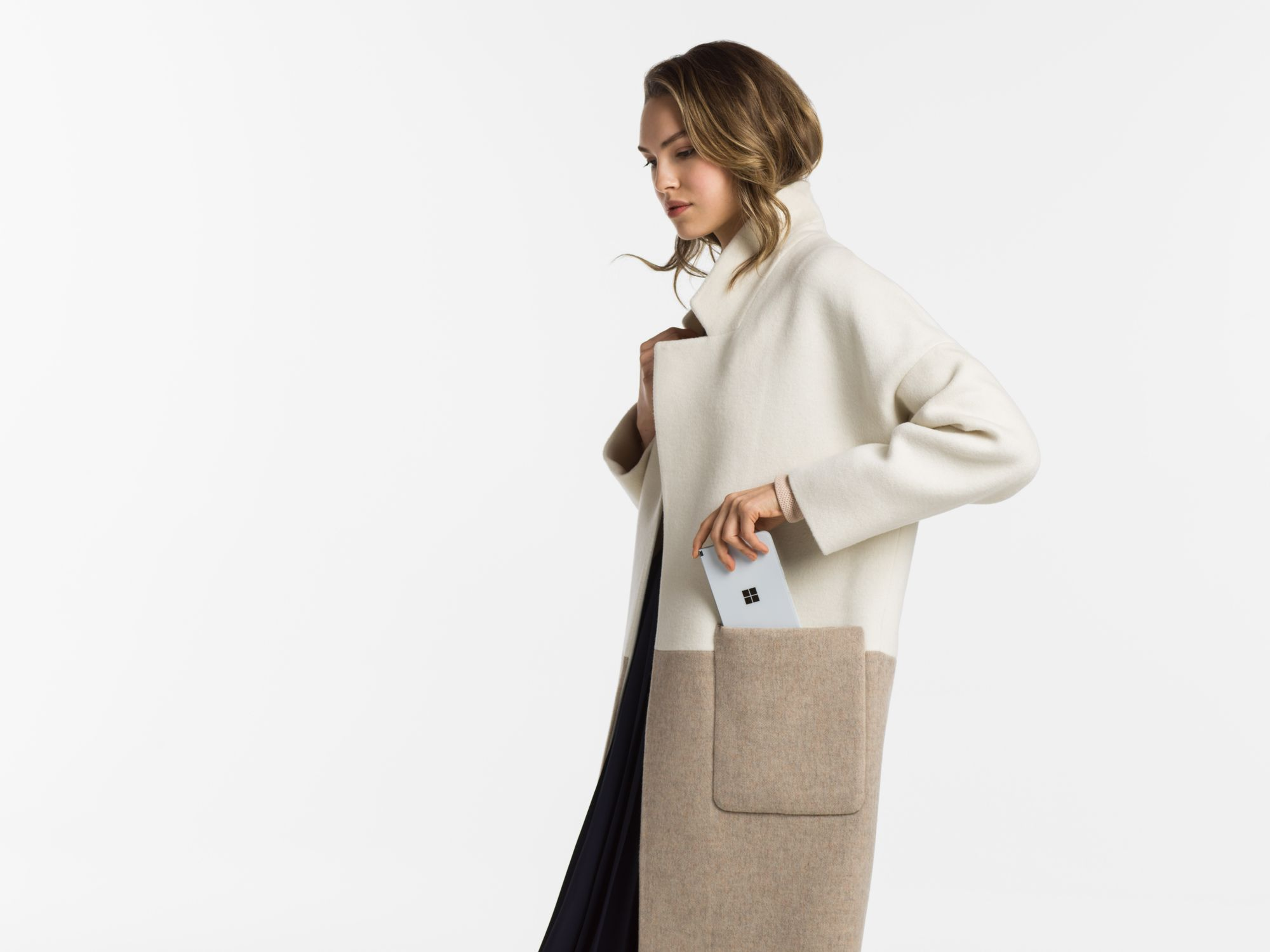 Eine Frau packt das Surface Duo in die Seitentasche Ihres Mantels